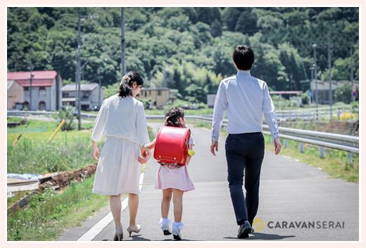 小学校入学記念のファミリーフォト 道を歩く親子3人の後ろ姿