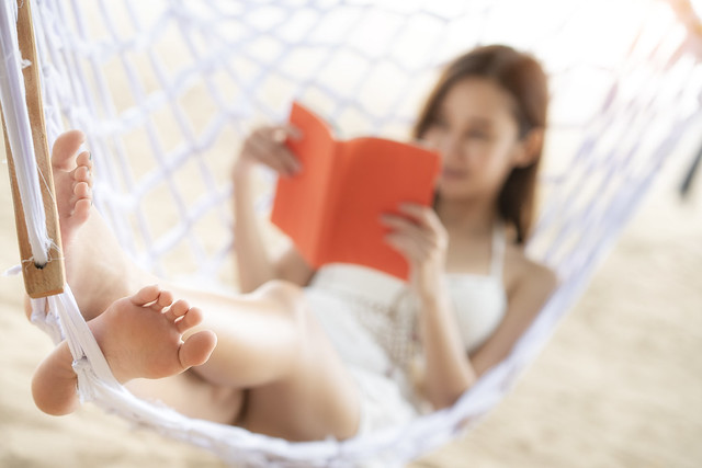 Asian girl sleep and reading on the beach thid image can use for travel, summer