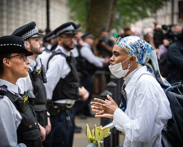 A protester debating with a police officer outside 10 Downing Street