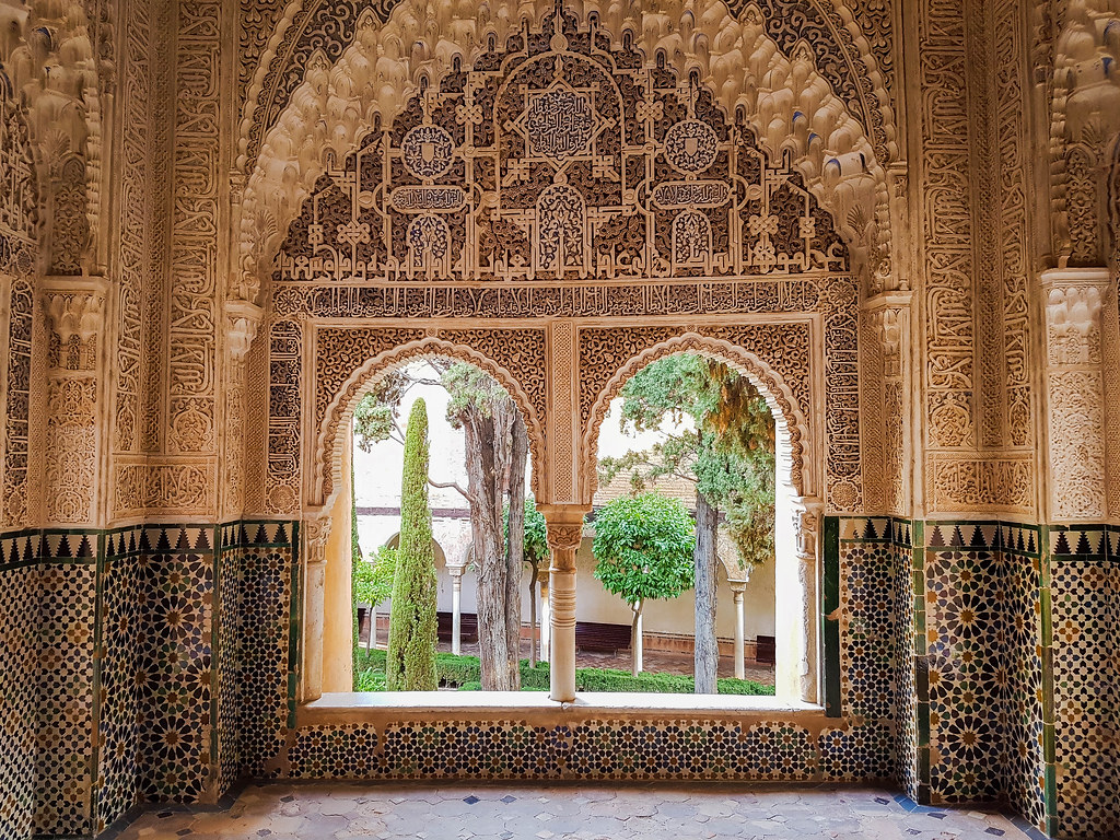 A window with an intricate design, inside the Alhambra. The walls around it have Arabic elements sculpted into them, both letters and geometrical patterns.