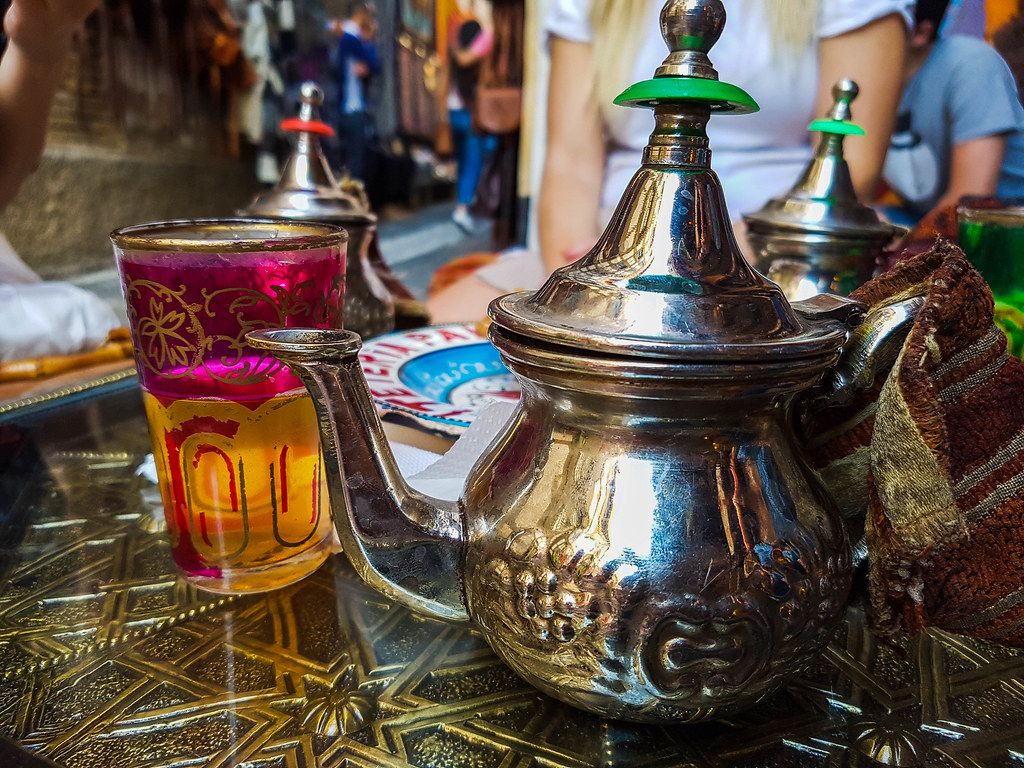 An Arabic metal tea pot next to a pink glass filled with yellow colored mint tea