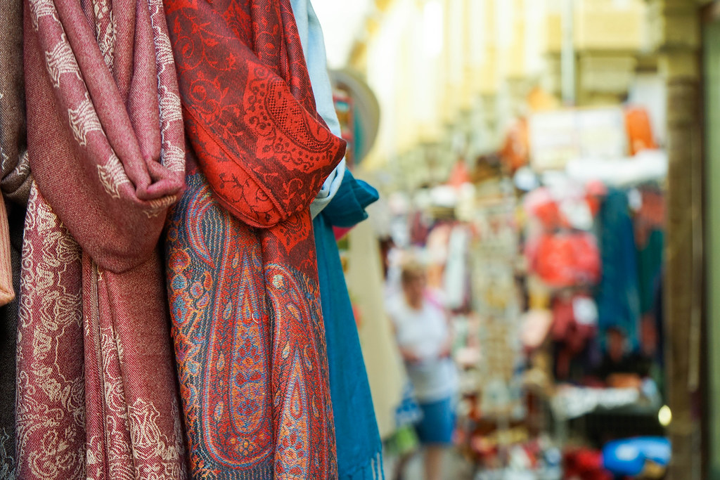 Three scarves: one blue, one red and one dark red, with a blury background of the market