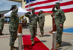 Capt. Allen Adkins walks through ceremonial side boys during the CRG 1 change of command ceremony. (U.S. Navy/BMC Nelson Doromal)