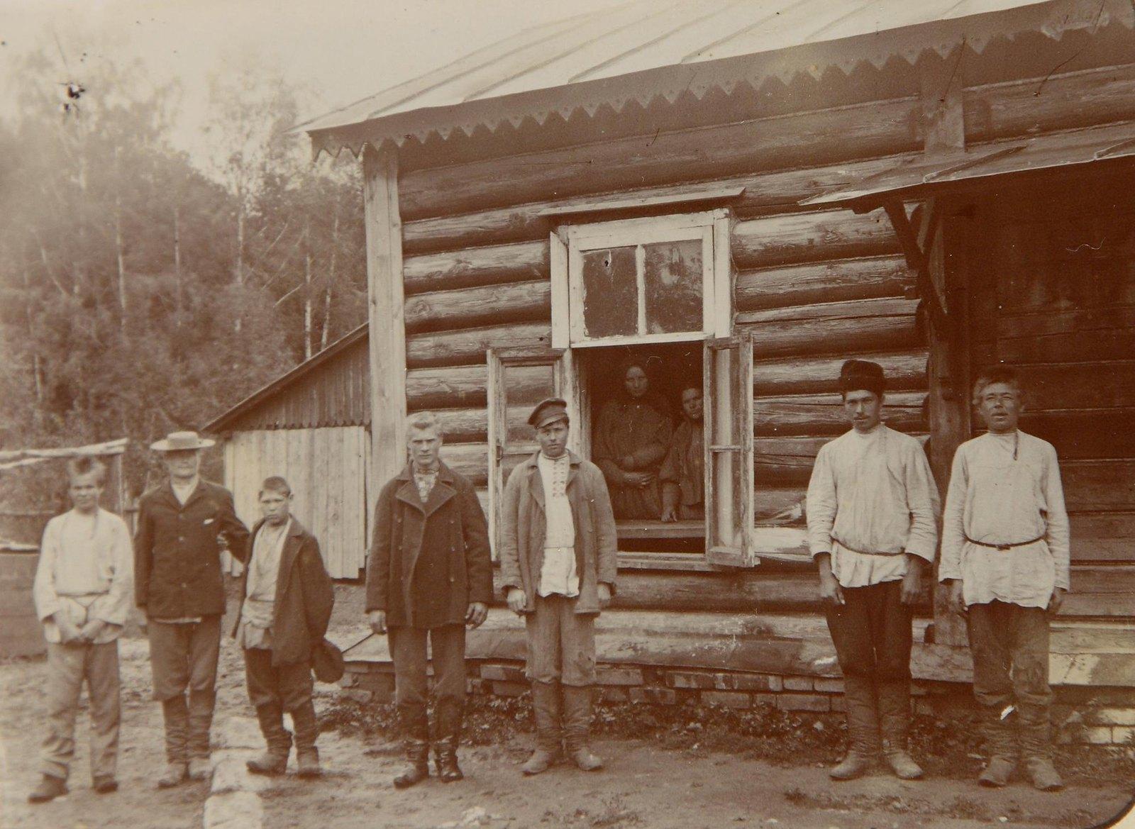 Группа мужчин у деревенского дома