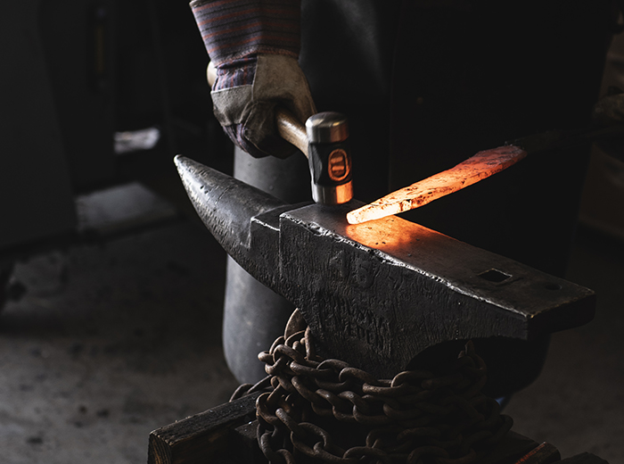 A hammer next to a glowing piece of metal on an anvil.