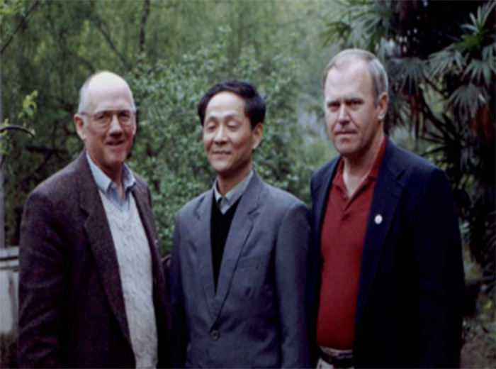 Three men stand together with trees and other plants in the background.