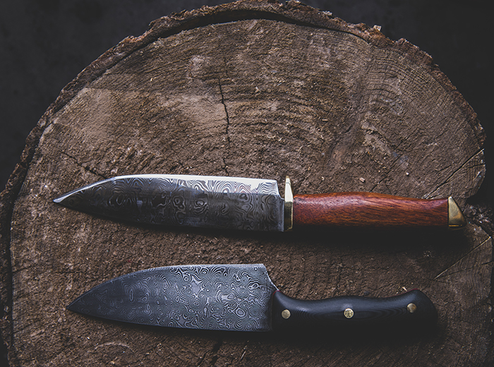 Two knives with intricate designs in the blades sitting atop a tree stump.