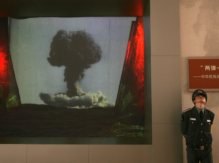 A man stands to the right of a screen showing an image of a mushroom cloud.