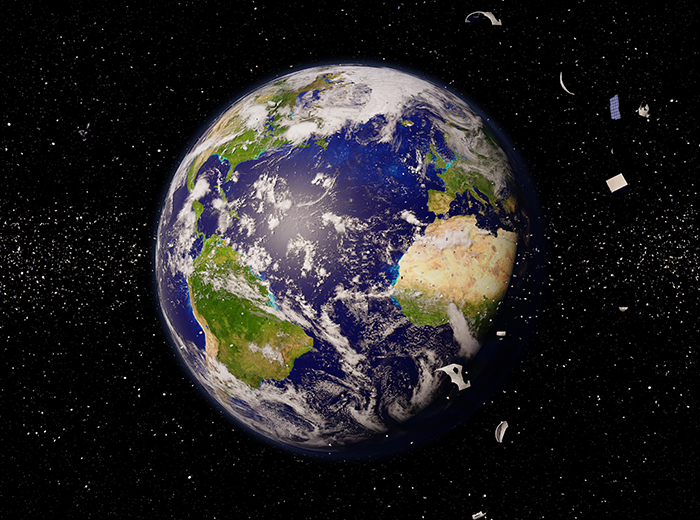 A photo of the earth with space in the background. Debris floats around in front of the Earth.