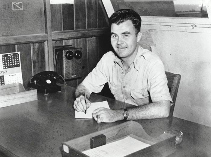 A man sits at a desk.