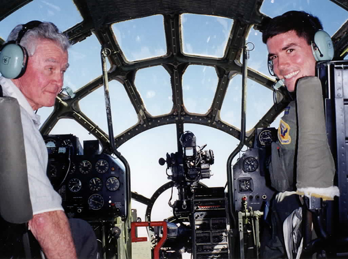 An older man and his son sit in the cockpit of a B-29 and look back at the camera.