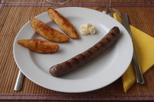 Frittierte Kartoffelecken zu gegrillter Rindsbratwurst