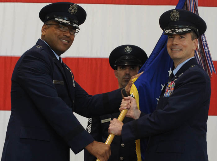 Two Air Force men holding a flag. A third man stands in the background.