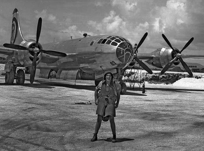 A man stands in front of a B-29 Superfortress aircraft.