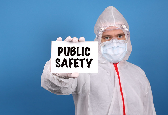 Medical doctor holding banner with Public Safety text, Isolated over blue background
