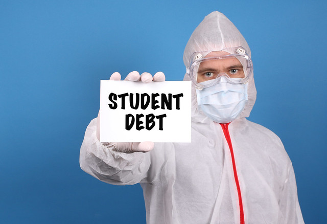 Medical doctor holding banner with Student Debt text, Isolated over blue background