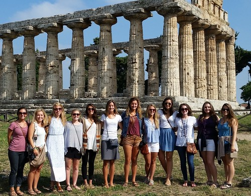 Group of university students stand outside a Greek temple in Paestum.