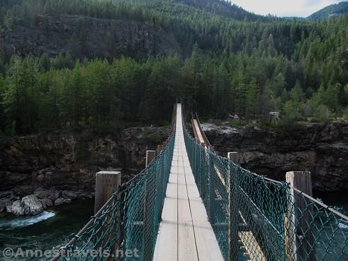 Walking across the old swinging bridge over the Kootenai River, Cabinet Mountains, Montana