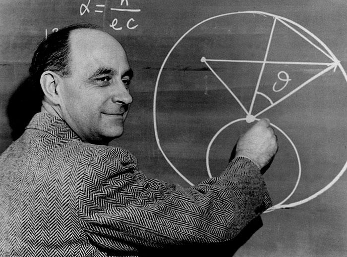 A man draws a diagram on a chalkboard.