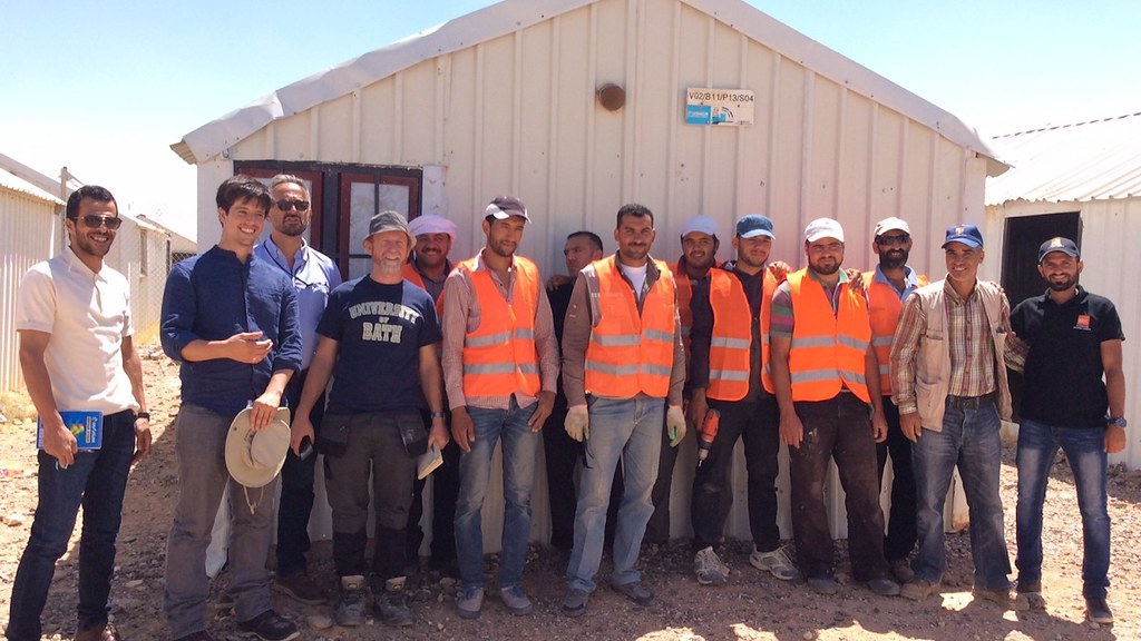 The Healthy Housing for the Displaced Project build team stands in front of a shelter in the Azraq camp in Jordan