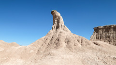 "A butte is a handle-shaped pillar of Oligocene deposits, with a ""toupée"" of prickly pear cactus."