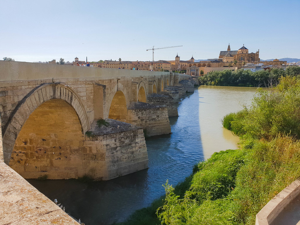The Roman bridge seen from the South side of the river, with the Mezquita in the background, over the water.
