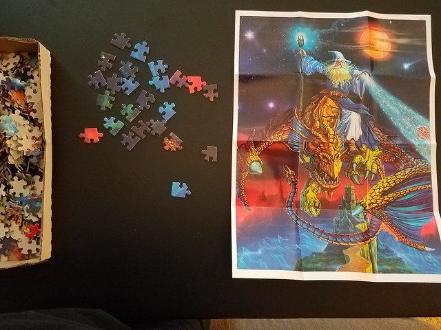 A puzzle of fantasy tropes including a wizard with a staff blasting something with magic while riding a dragon and protecting a castle with a comet and a moon thrown in for good measure.
