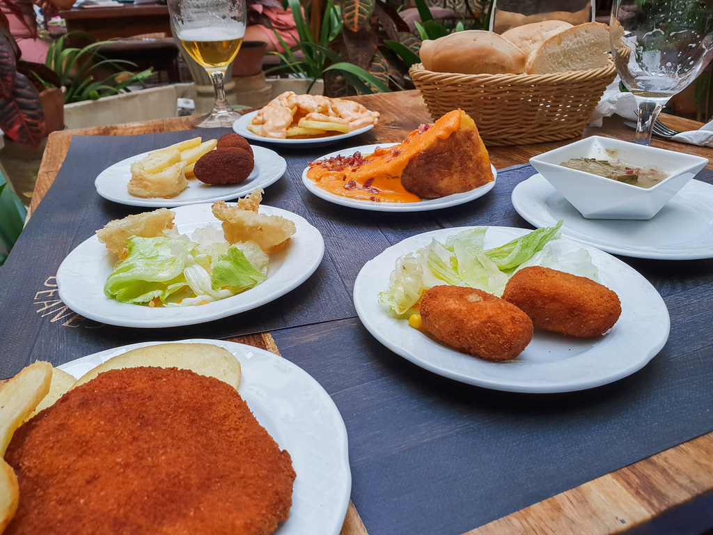 A photo of the table filled with small tapas plates: a tortilla de patatas covered in orange salmorejo with pieces of red jamon on top, two plates of crunchy croquettes, one with green salad and the other one with french fries, friend potatoes covered in a pink bravas sauce.