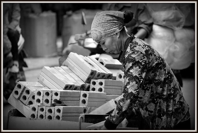 Une livreuse de briques a Hanoi.