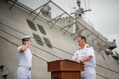 Cmdr. William Dvorak, the executive officer of USS Kansas City (LCS 22), salutes commanding officer Cmdr. R.J. Zamberlan during a reading of his orders as part of the ship's commissioning ceremony. (U.S. Navy/MC2 Alex Corona)