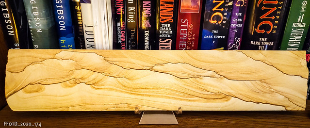 Sandstone plank in stand on bookshelf in front of books