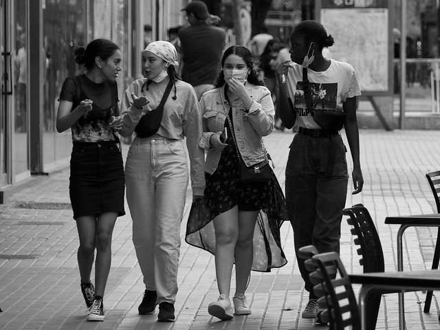 Noies maques, alguna amb mascareta, xerren i caminen per l'avinguda del Paral.lel, Barcelona.