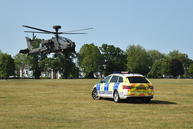 Face off between Apache Helicopter and Military Police Car
