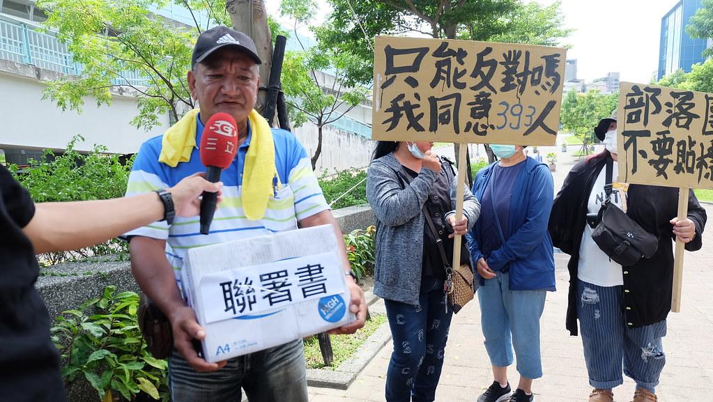 知本建業里里長王正元(左一)與民眾高舉「不要訴訟、不要訴願」、「部落團結不要貼標籤」的牌子表達另一方意見。攝影:陳文姿