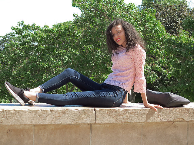 Curly girl in tight jeans posing on the parapet