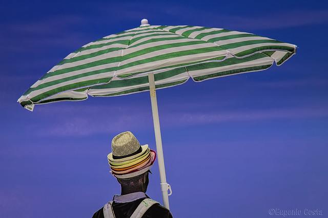 Venditore ambulante di ombrelloni.  Street vendor of umbrellas.