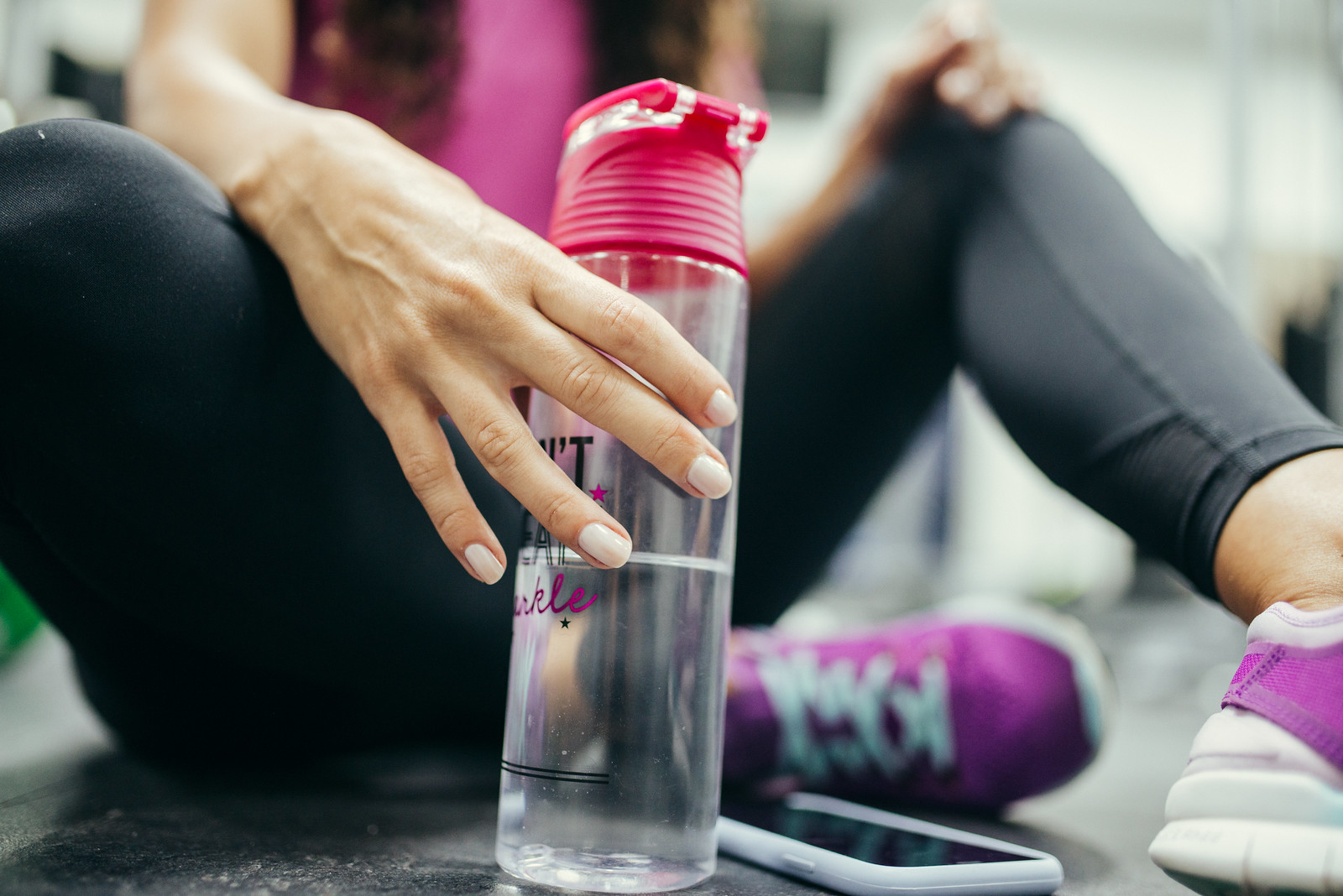Close-up picture of woman with bottle of water and her phone sitting in gym