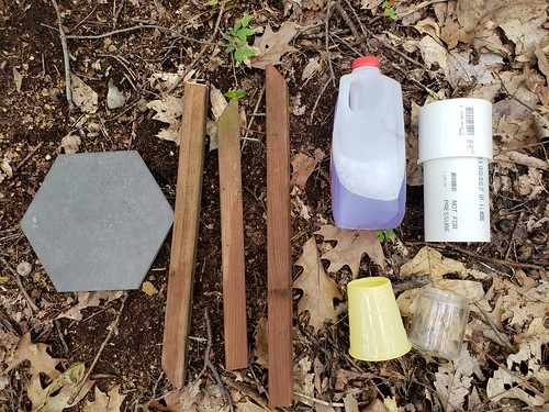hexagonal bathroom tile, 3 pieces of one by one wood railing from a deck, a plastic half gallon jug with preservative, plastic cup with bottom cut out, eight ounce glass cup, and eight or nine inch section of PVC drain pipe; all parts lay spread out on forest floor
