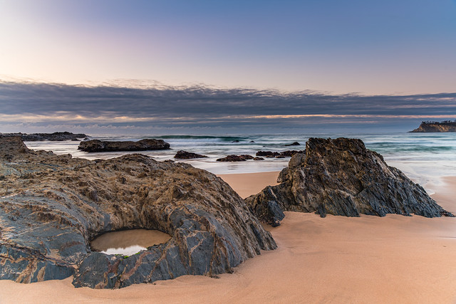 Sunrise seascape with rocks and low cloud bank