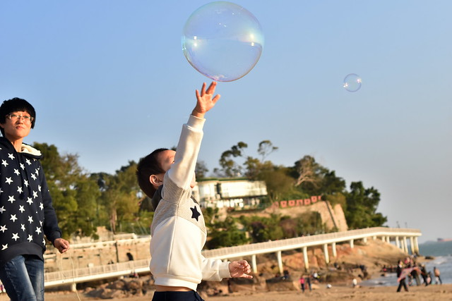 Mother-son bubble time at the beach, Xiamen, China