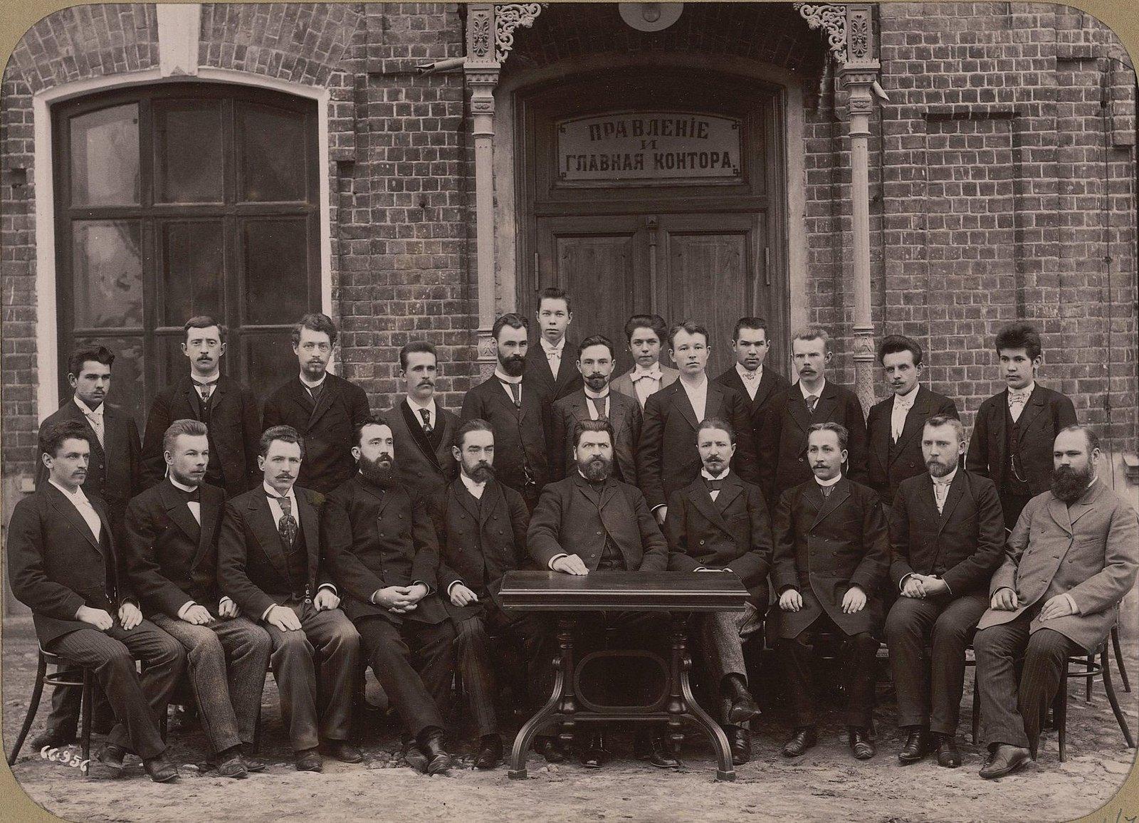 07.  Главный бухгалтер и сотрудники конторы на фоне входа в здание правления и главной конторы