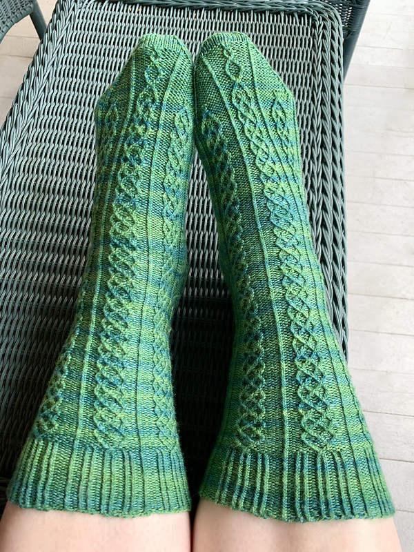 Walking through a Vineyard Socks, shown on feet outdoors to demonstrate the stitch pattern as worn.