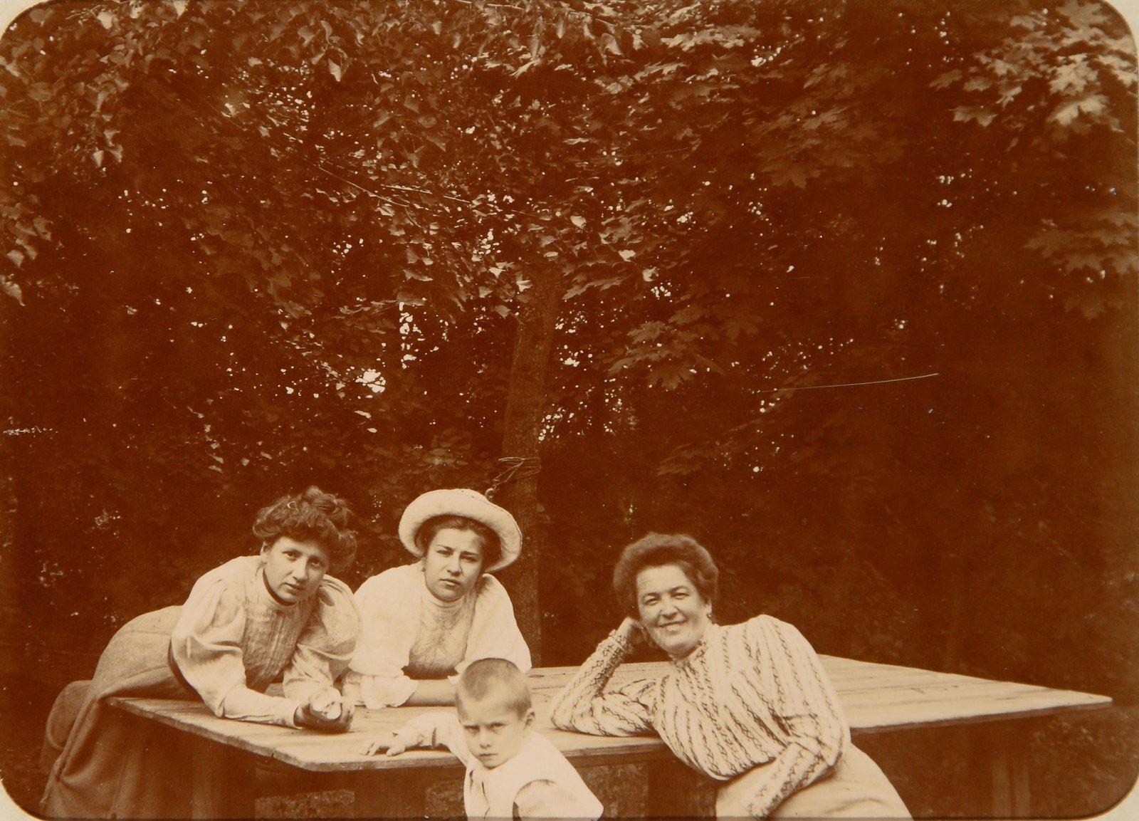 02. Три дамы с мальчиком за деревянным столом в парке