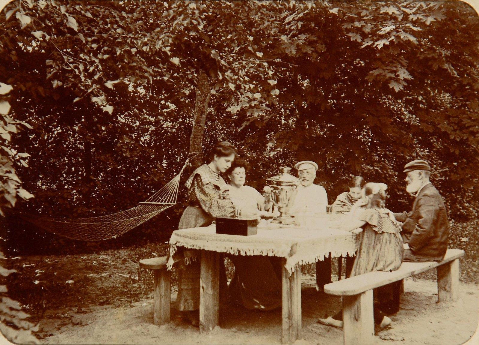 01. Пьют чай за деревянным столом в парке