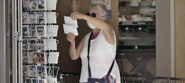 Campan (Hautes-Pyrénées, Occitanie Fr) – Portrait au masque, une touriste achète des cartes postales.