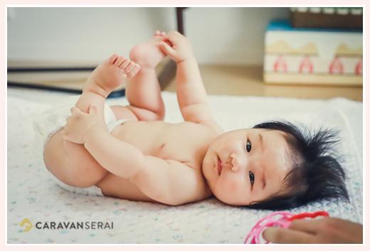 オムツ姿の赤ちゃん 手で自分の足をつかむ姿