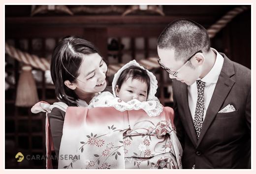 お宮参り 赤ちゃんを覗きこむパパとママ 産着