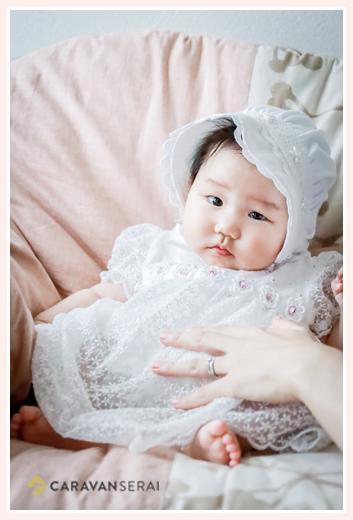 ベビードレスを着た赤ちゃん ママの支えてお座りポーズ