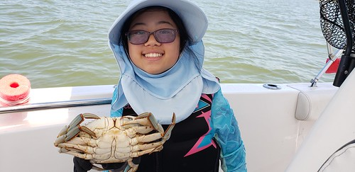 Photo of girl holding a large blue crab she caught