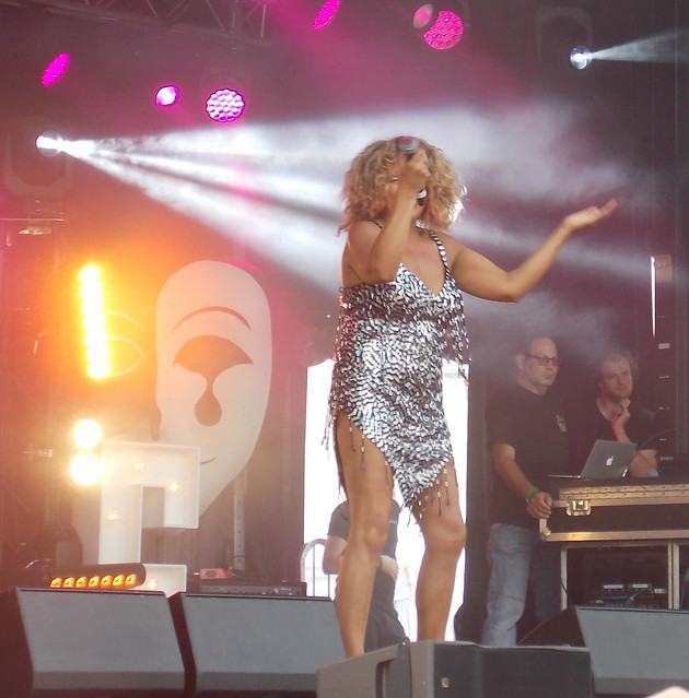 TINA TURNER TRIBUTE ARTIST WEARING A SILVER DRESS SHAKING SOME MOVES SINGING ENTERTAINING WITH LONG HAIR MOVING FLYING IN THE AIR   AT A MUSIC FESTIVAL IN AN EAST LONDON BOROUGH SUBURB STREET PARK VENUE ENGLAND  DSCN2042
